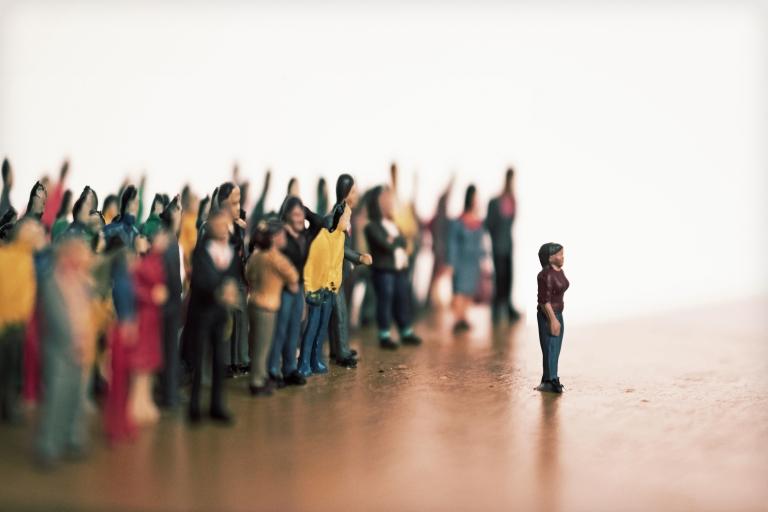 Joukko ihmisiä pilkkaa ja huutaa yksin seisovalle ihmiselle