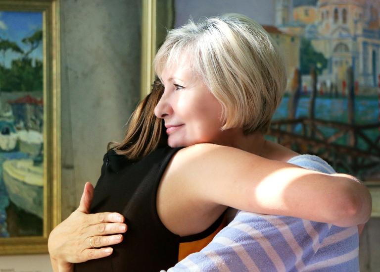 Äiti halaa tytärtä.