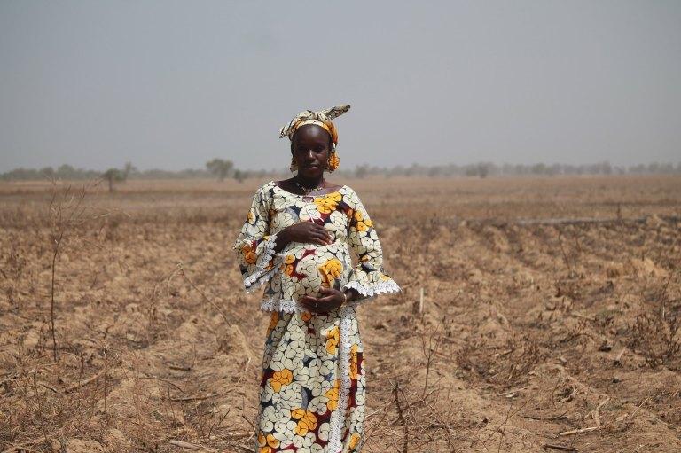 Afrikkalainen raskaana oleva nainen seisoo pellolla