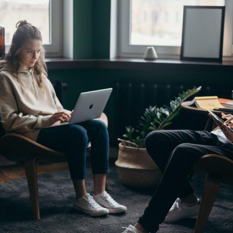 Mies ja nainen työskentelevät tietokoneilla kotonaan