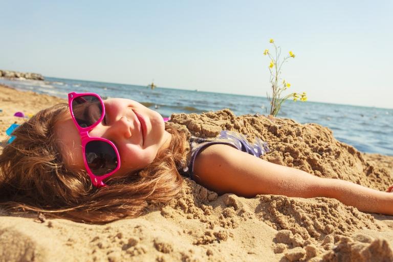 Pieni tyttö makaa kesäisellä rannalla hautautuneena hiekkaan, aurinkolasit päässä ja hymyilee kameraan