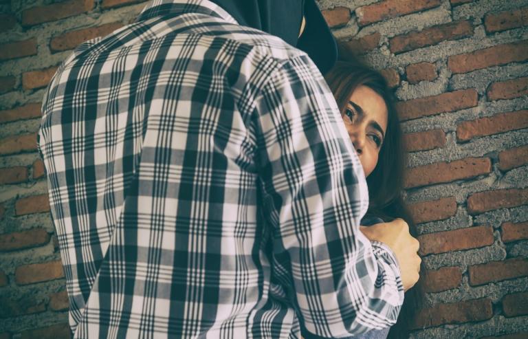 Kuvituskuva, jossa mies on ahdistanut naisen tiiliseinää vasten