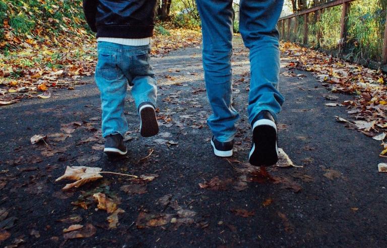 Aikuisen ja lapsen jalat näkyvät takaapäin, kun he kävelevät syksyisellä tiellä