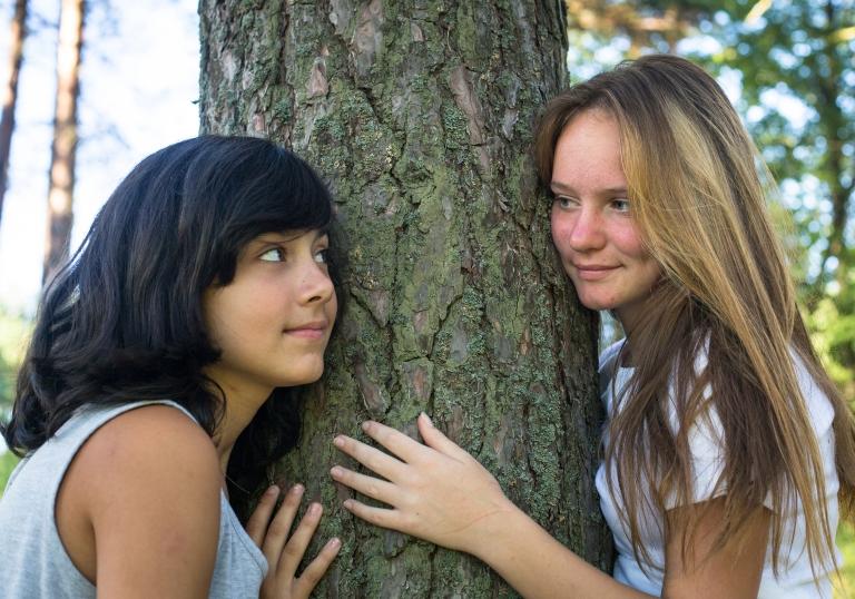 Kuvassa kaksi nuorta tyttöä, jotka nojaavat puuhun ja katsovat toisiaan