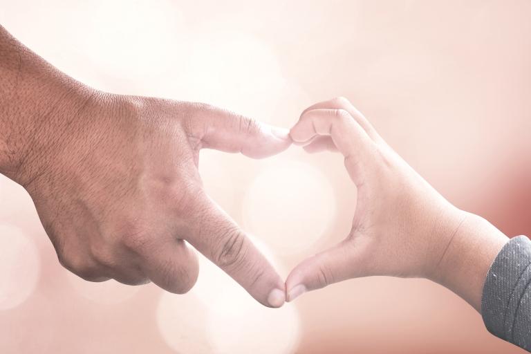 Miehen ja lapsen sormet muodostavat yhdessä sydämen kuvan.