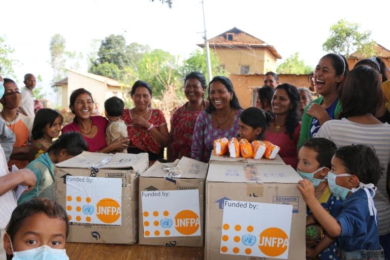 Ehkä afrikkalaisia, iloitsevia naisia UNFPAn eli YK:n väestörahaston toimittamien laatikoiden takana.