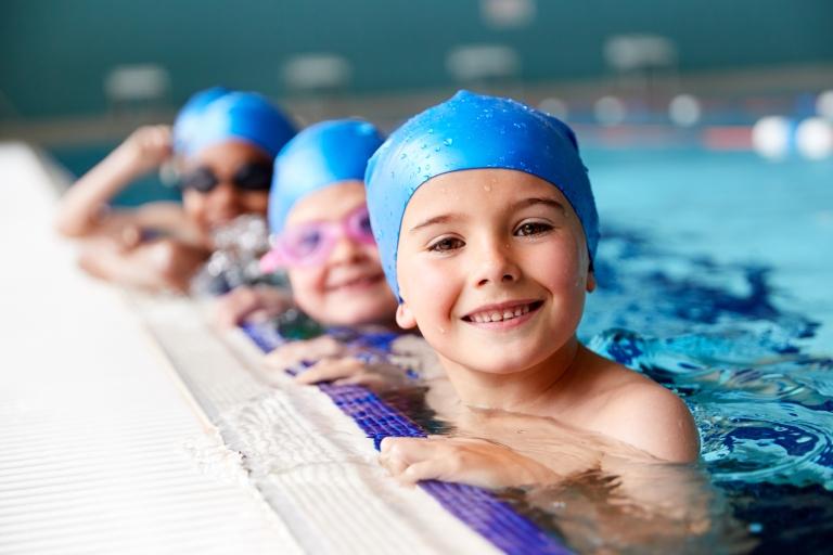 Kolme nuorta lasta uimahatut päässä altaan reunalla.