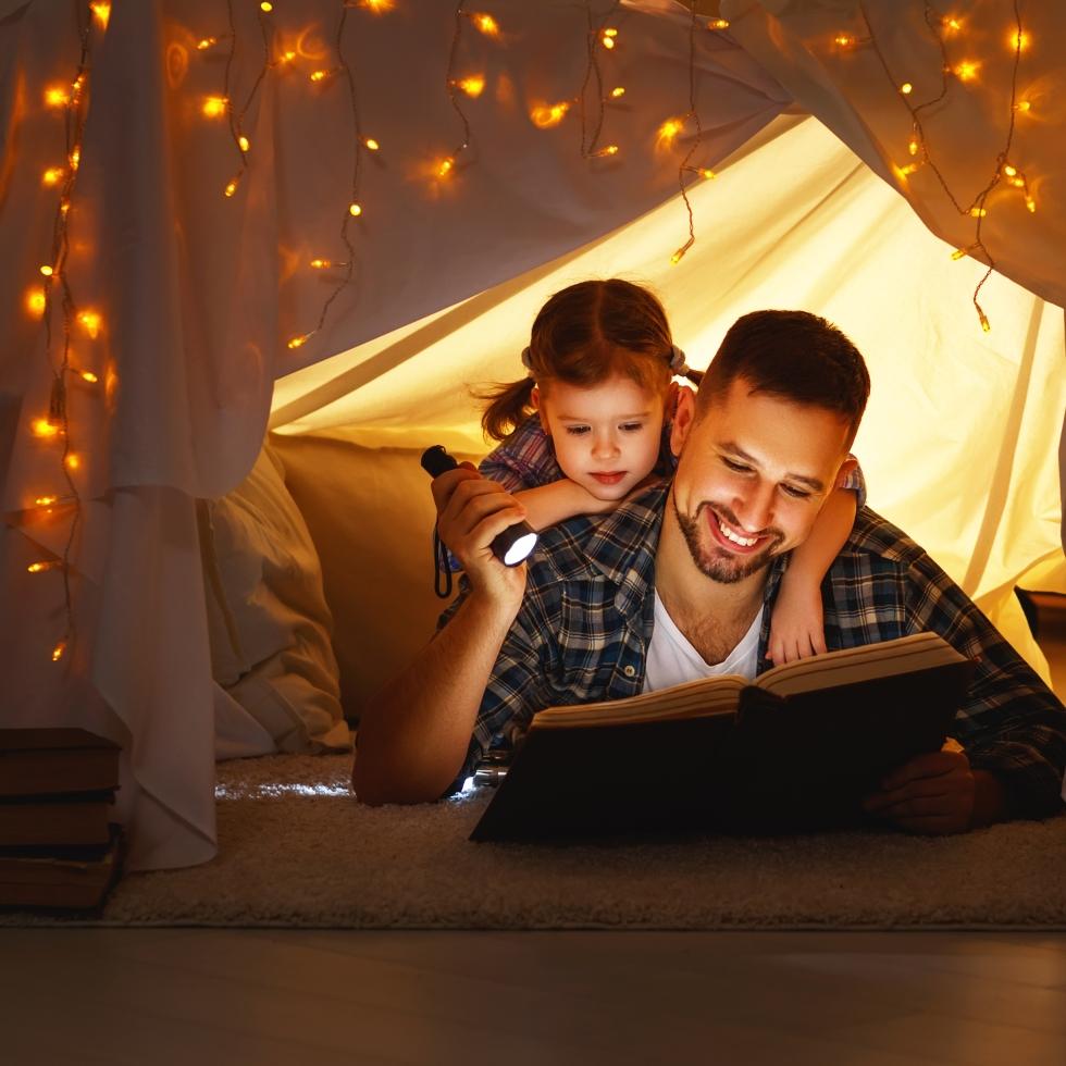 Isä ja lapsi makaavat sisällä teltassa ja isä lukee lapselle kirjaa.