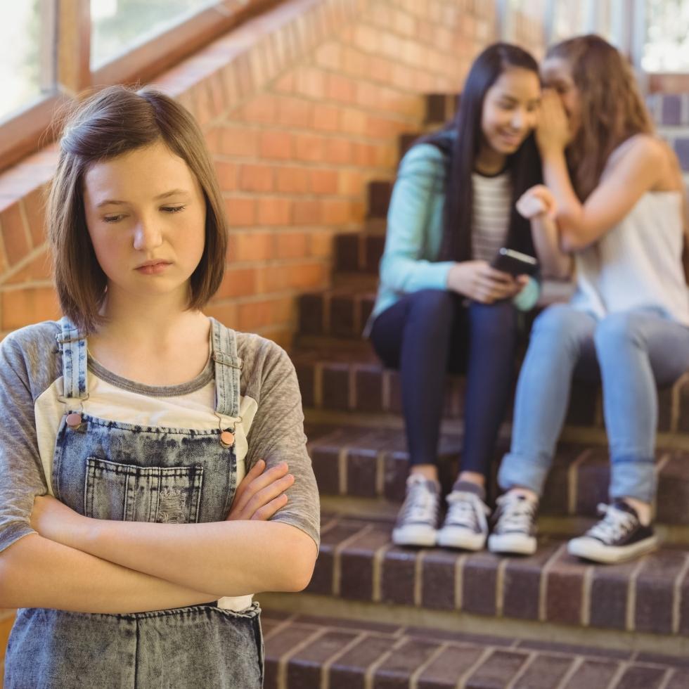 Koulutyttö on surullinen, kun kaksi ystävää kuiskuttelee hänestä hänen selkänsä takana.