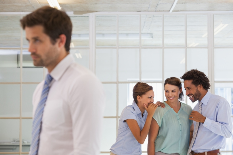 Kiusaamistilanne työpaikalla, joukko muita kuiskuttelee yhden henkilön takana.