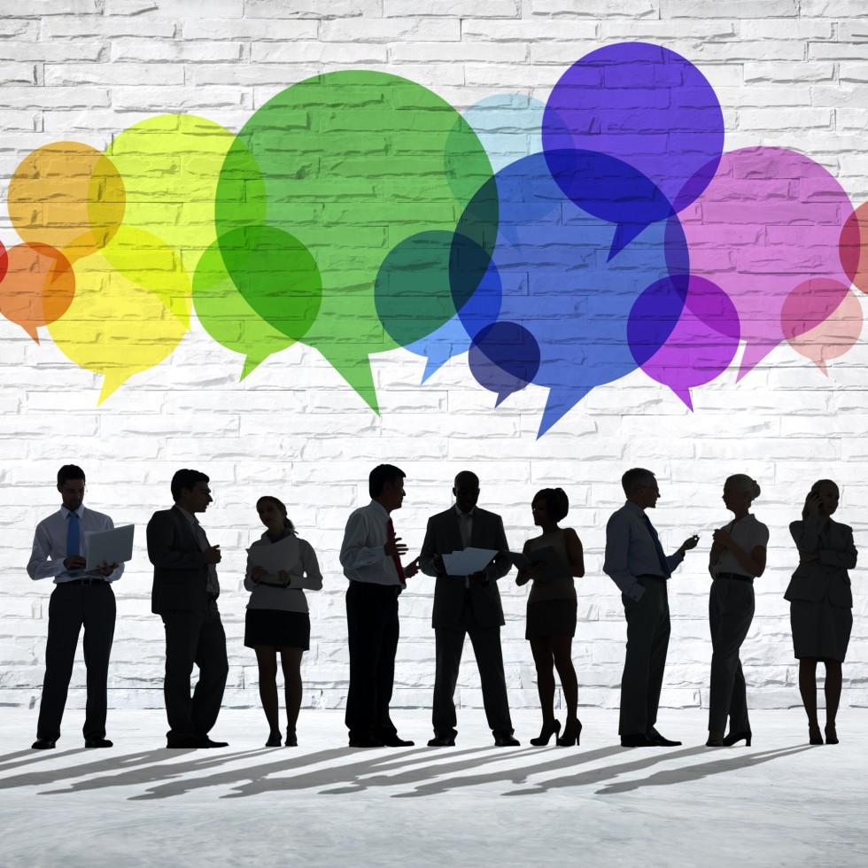 Siluettikuva ihmisistä, joiden päällä erivärisiä puhekuplia, jotka voivat symboloida eri kieliä.