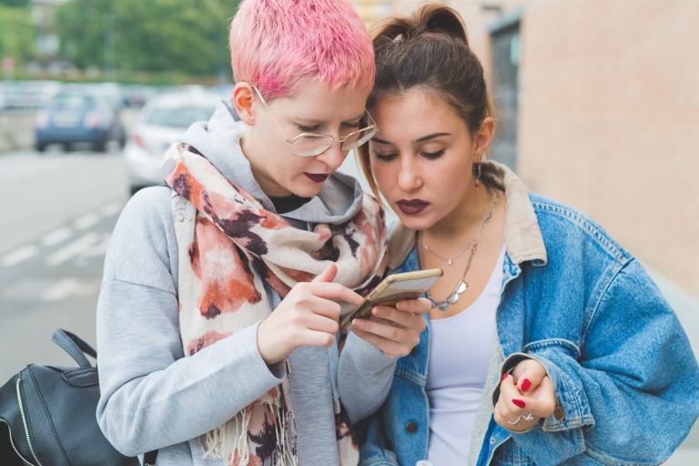 Kaksi nuorta tyttöä lukee jotain kännykästä.