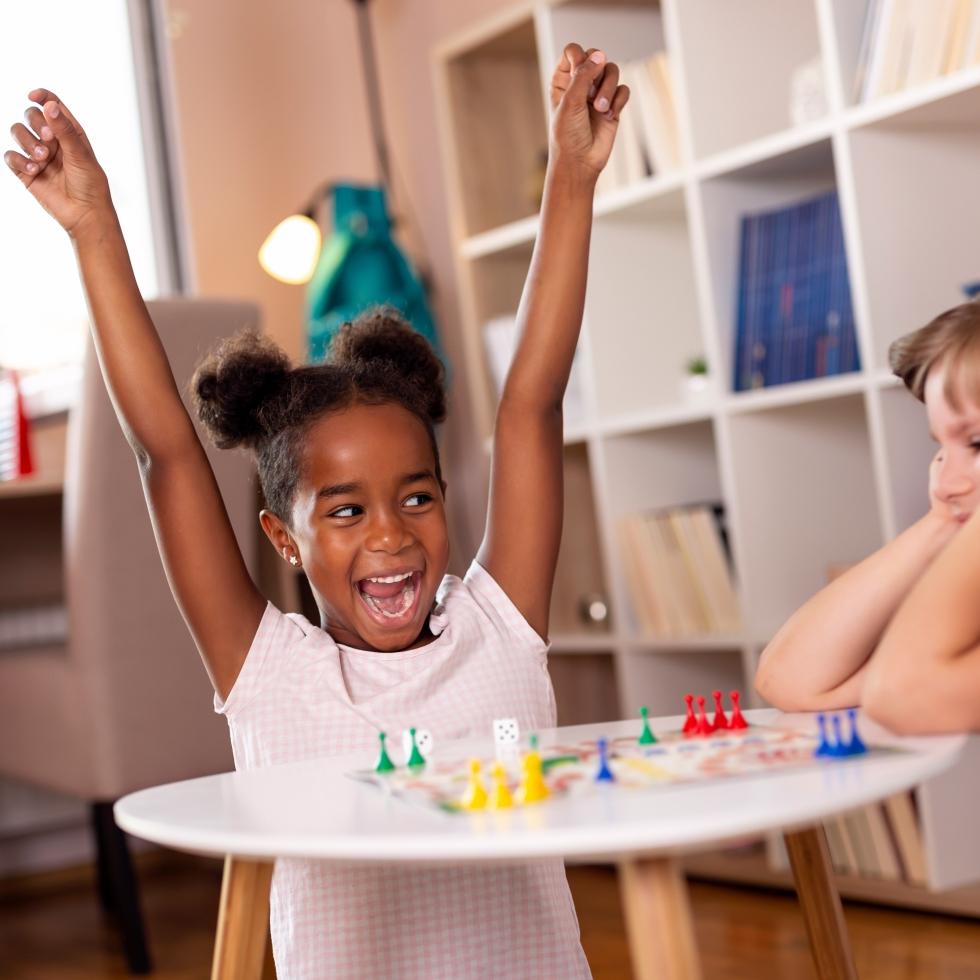Kaksi pientä tyttöä pelaa lautapeliä, toinen riemuitsee voitostaan, toinen vaikuttaa hieman pettynyneeltä.