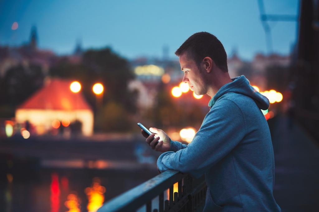 A man is looking at his phone on balcony.  Mies katsoo puhelintaan parvekkeella.