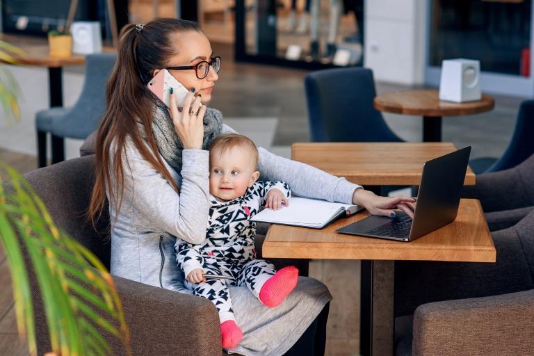 Nuorisäiti istuu kirjastossa lapsi sylissään, puhuu kännykässä ja läppäri on auki edessä.