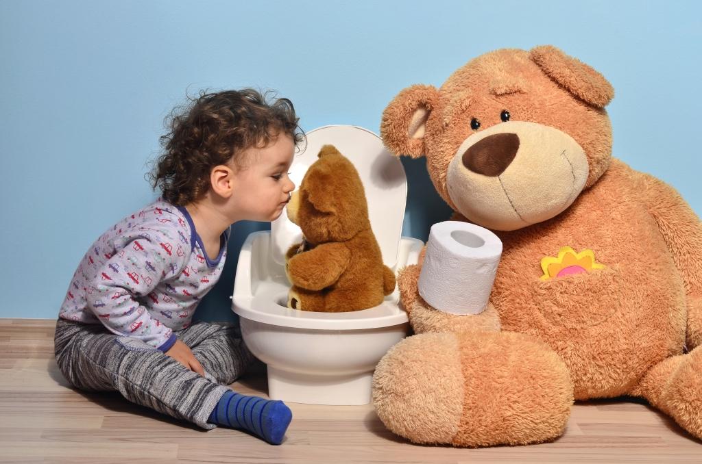 Pieni lapsi pussaa vessanpöntöllä istuvaa pientä nallea. Vessanpöntön oikealla puolella istuu iso nalle, joka pitelee kädessään vessapaperirullaa.