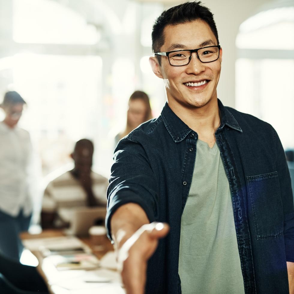 Mies työpaikalla, ojentaa kättään tervehdykseen. Muita työkavereita istuu taka-alalla.