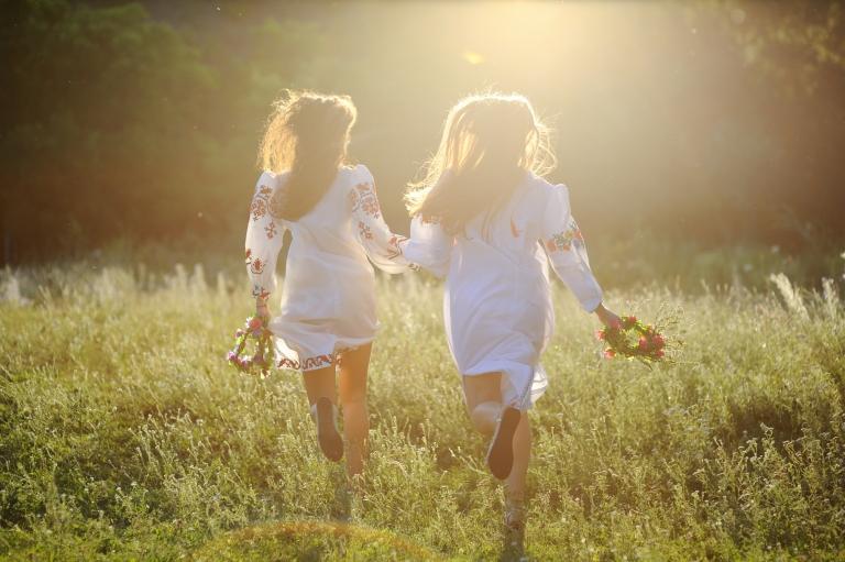 Kaksi naista juoksee niityllä kukkaseppeleet kädessään.
