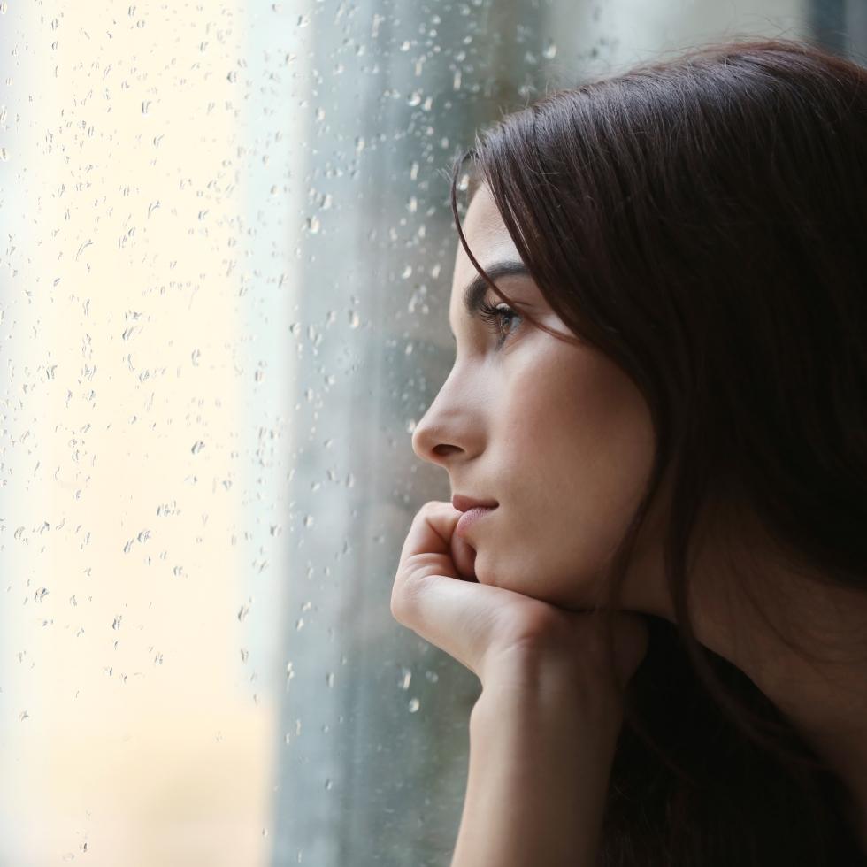 Nainen katselee mietteissään ulos sateisesta ikkunasta.