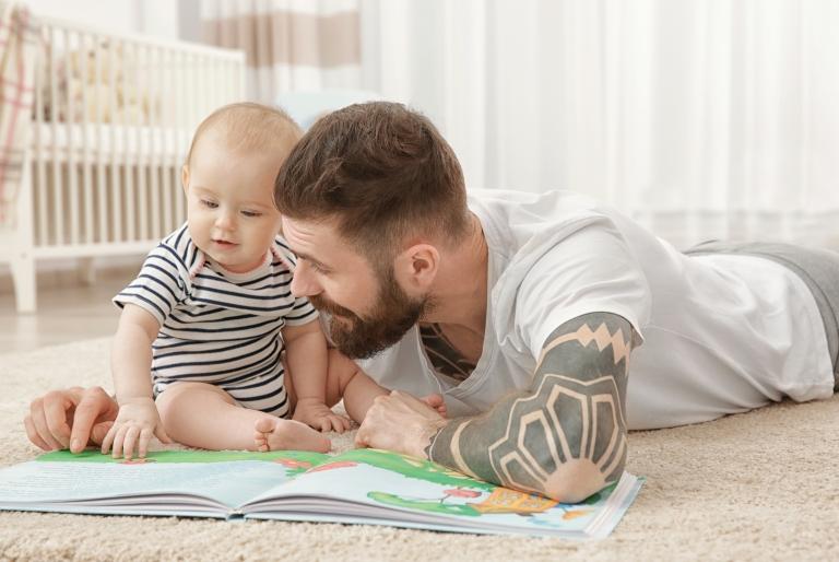 Isä ja vauva lattialla katsomassa kuvakirjaa.