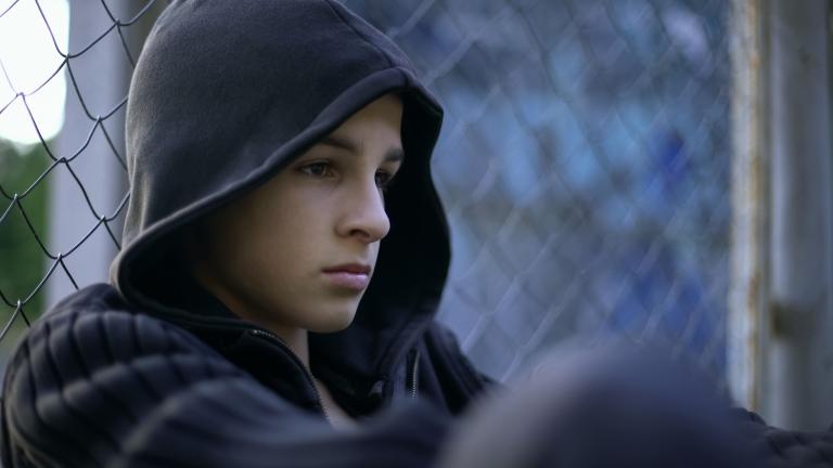 Yksinäinen poika istuu ajatuksissaan ja katselee eteenpäin.