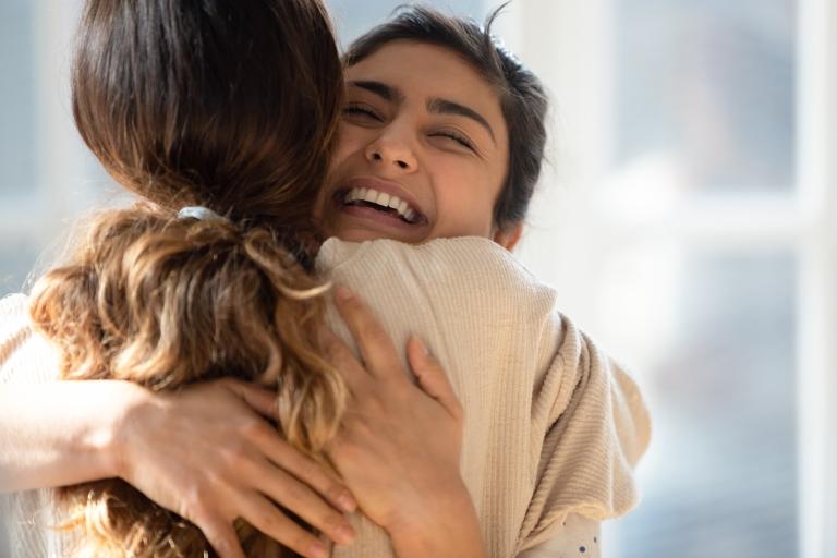 Kaksi naista halaa toisiaan, ehkä jälleennäkemisen riemussa.