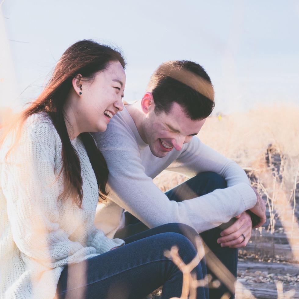 Nuori nainen ja mies istuvat ulkona ja nauravat yhdessä.