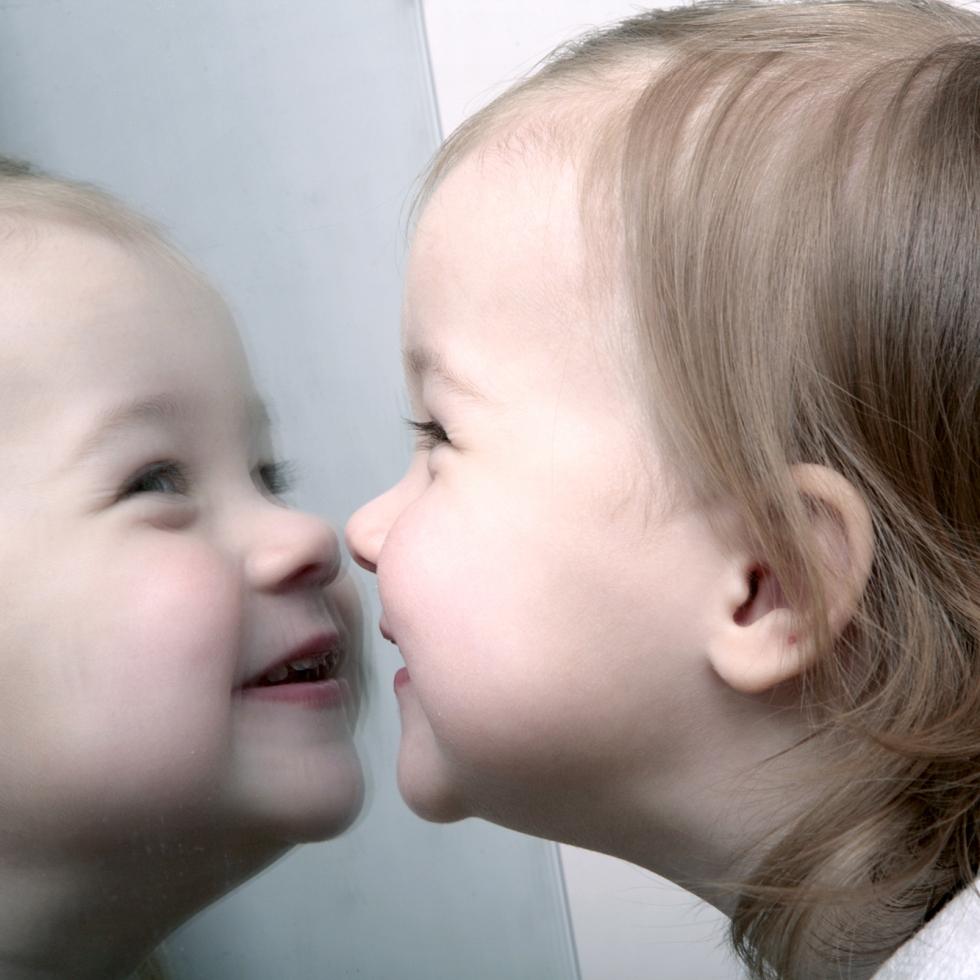 Pieni lapsi ihailee itseään peilistä.