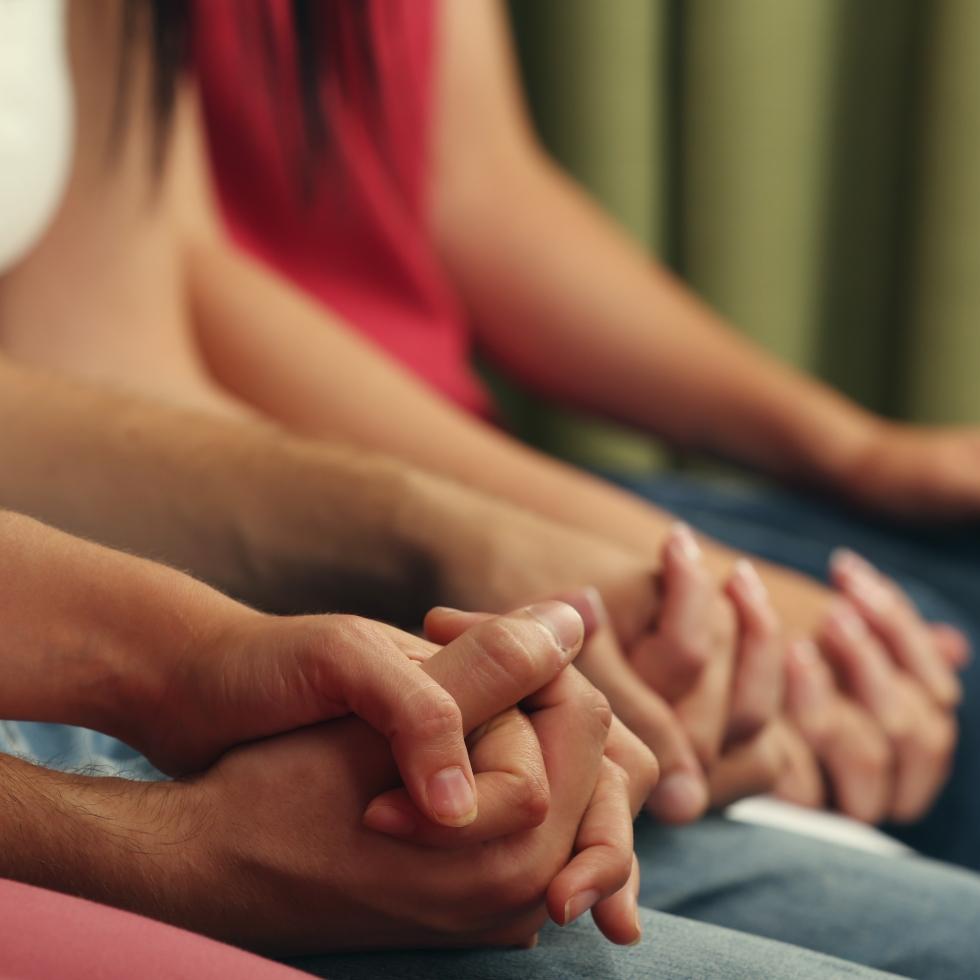 Kuva istuvista nuorista, jotka pitävät toisiaan käsistä. Kuvassa ei näy kasvoja, ainoastaan kädet.