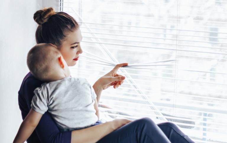 Nuori, alakuloisen näköinen äiti vauva sylissään  raottaa sälekaihtimia ja katsoo ikkunasta ulos.